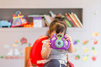 Preschooler playing with a camera at Cal Ivy Prep School in Bakersfield